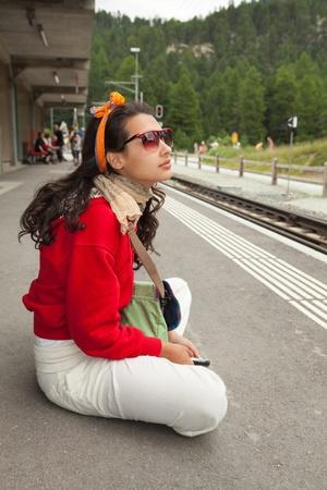 swiss alps: Dość młoda kobieta czeka na pociąg w Alpach szwajcarskich