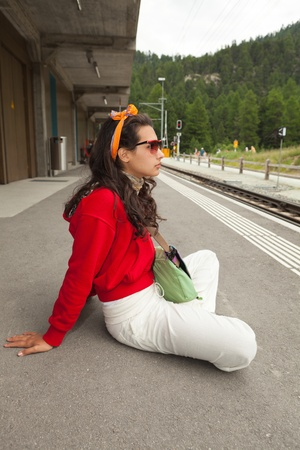 Pretty young woman waiting for a train in the Swiss Alps photo