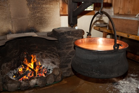 making a fire: Large milk cauldron for making cheese in farm house