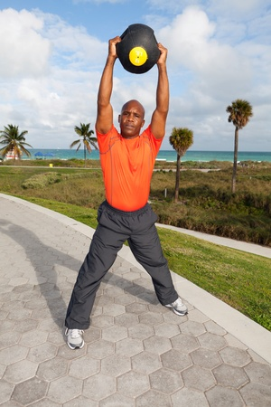 Handsome personal trainer exercising in Miami South Beach park Stock Photo - 11928057