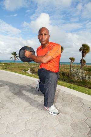 medicine ball: Handsome personal trainer exercising in Miami South Beach park