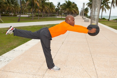Handsome personal trainer exercising in Miami South Beach park photo