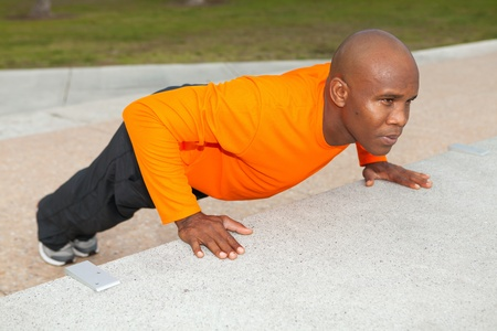 Handsome personal trainer exercising in a South Beach park in Miami Stock Photo - 12026100