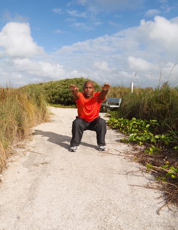 Handsome personal trainer exercising in a South Beach park in Miami Stock Photo - 12026082