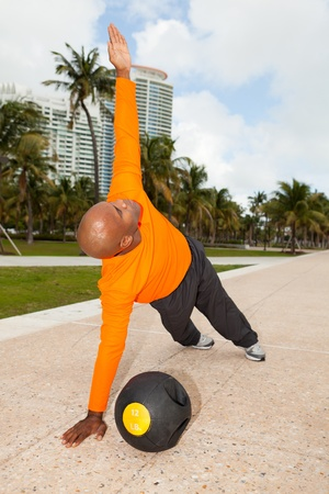 Handsome personal trainer exercising in a South Beach park in Miami photo