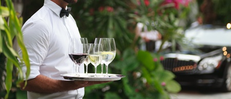 Tuxedo dressed waiter serving wine photo