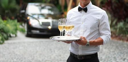 Tuxedo geklede ober serveert champagne