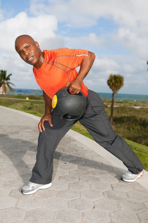 Handsome personal trainer exercising in Miami Beach photo