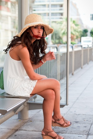 Beautiful young woman waiting for a bus in the French Riviera Stock Photo