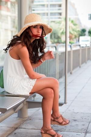 Mooie jonge vrouw te wachten op een bus in de Franse Rivièra Stockfoto