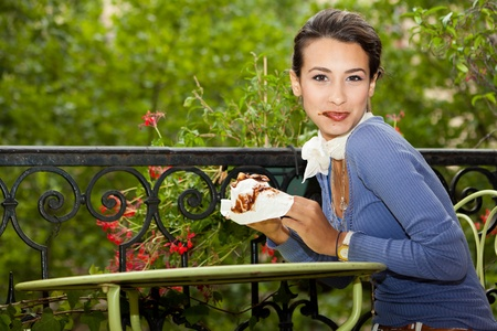 Beautiful young woman enjoying a chocolate croissant on a Paris balcony photo