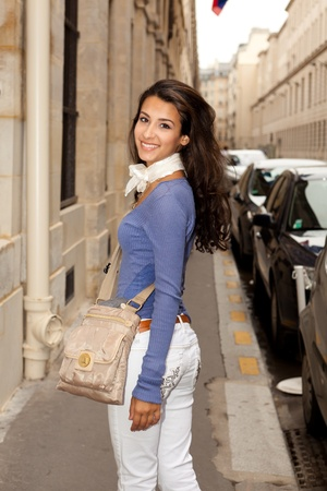 Pretty young woman strolling along a Paris sidewalk photo