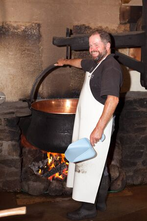 making a fire: Swiss man making cheese in a farm house Editorial