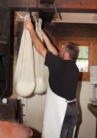 swiss cheese: Swiss man making cheese in a farm house Editorial