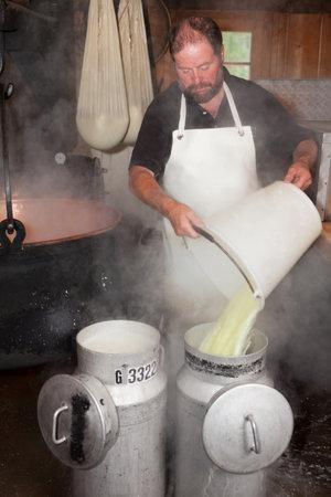 Swiss man making cheese in a farm house Editorial