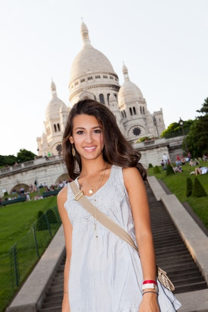 montmartre: Beautiful young woman enjoying the sights of Paris with the Sacre Coeur Cathedral in the background in the Montmartre area
