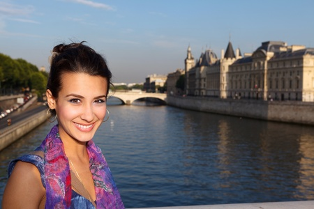 french ethnicity: Beautiful young woman enjoying the sights of Paris along the River Seine