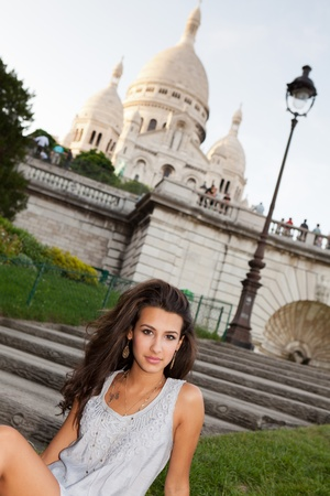 middle eastern ethnicity: Beautiful young woman enjoying the sights of Paris with the Sacre Coeur Cathedral in the background in the Montmartre area