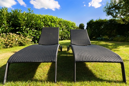 residence: Pair of wicker lounge chairs in a residence back yard Stock Photo