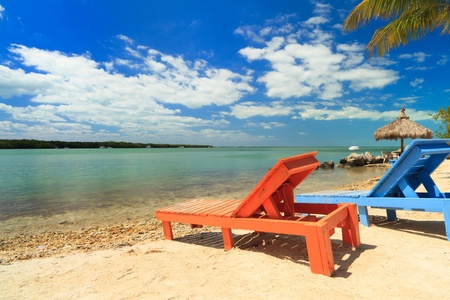 Wooden beach lounge chairs along the shoreline of the Florida Keys with pretty blue sky and clouds and thatched hut in the background