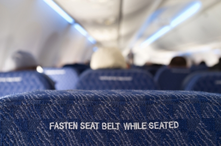 fasten: Fasten seat belt sign on the back of a seat from a commercial airliner