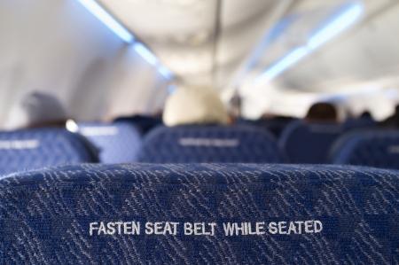 Fijar se�al del cintur�n de seguridad en la parte posterior de un asiento de un avi�n comercial photo