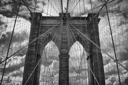 Dramatic black and white view of the historic Brooklyn Bridge with ominous clouds in the background