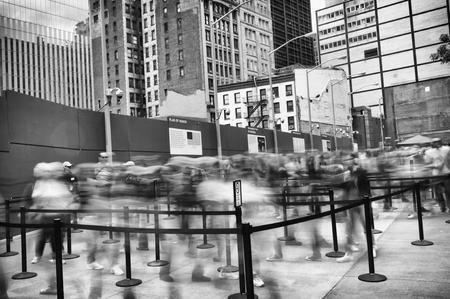 Dramatic black and white view of the entrance to the 9 11 Memorial in Manhattan, New York with a long line of visitors in blurred motion entering the site