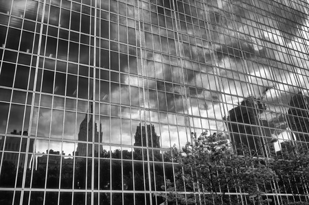 manhattan mirror new york: Dramatic black and white view of the downtown Manhattan skyline reflected from a mirrored glass office building