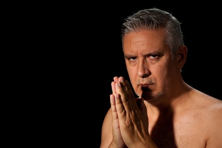 barechested: Handsome unshaven middle age man with salt and pepper hair and barechested with hands together in a prayer pose on a black background.