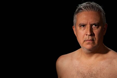 barechested: Handsome unshaven middle age man with salt and pepper hair and barechested on a black background.