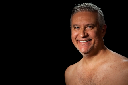 bare chested: Handsome unshaven middle age man with salt and pepper hair and barechested on a black background.