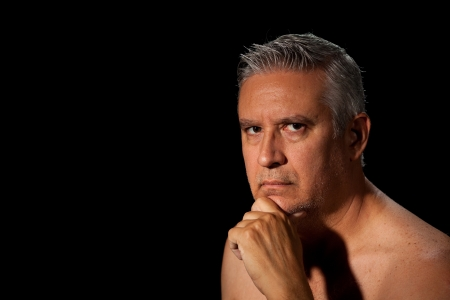 Handsome unshaven middle age man with salt and pepper hair and barechested on a black background.