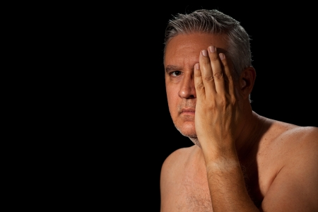 Handsome unshaven middle age man with salt and pepper hair and barechested covering one eye on a black background. photo
