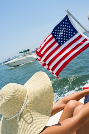 american flag waving: Young woman on a boat wearing a big hat with American flag waving and boat passing by