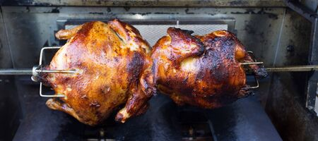 Rotisserie chicken cooking in a gas grill Stock Photo