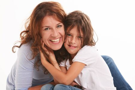 kids hugging: Mother and daughter in a loving pose isolated on a white background  Stock Photo