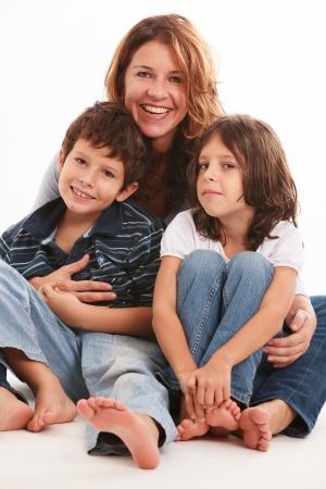 pies descalzos: Bastante joven madre con el hijo y la hija aislado en un fondo blanco Foto de archivo