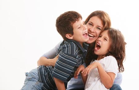 madre soltera: Madre bastante joven con el hijo y la hija de una manera divertida pose aislado en un fondo blanco