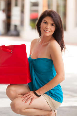 Beautiful woman outdoors in a shopping mall holding a red bag. Stock Photo - 14743114