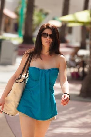 Mooie vrouw een wandeling langs een openlucht winkelcentrum. Stockfoto