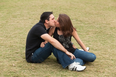Young married couple  in a loving pose sitting on a lawn in a park  photo