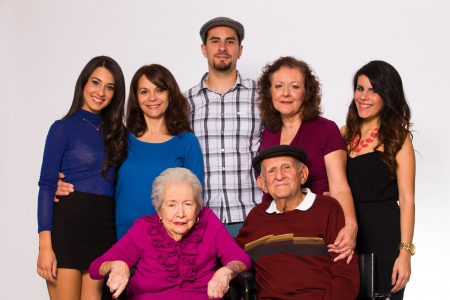 Family posing with elderly grandparents on a white background