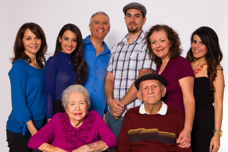 latinos: Family posing with elderly grandparents on a white background