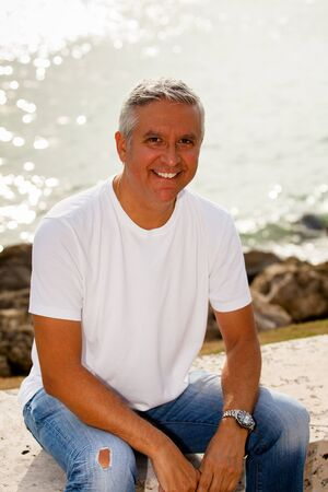 south american: Handsome middle age man in casual clothing enjoying a park setting by the bay  Stock Photo