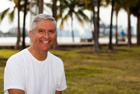 Knappe middelbare leeftijd man in casual kleding genieten van een parkachtige omgeving Stockfoto