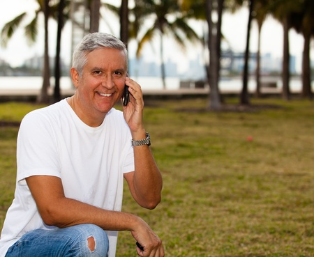 casual clothing: Handsome middle age man in casual clothing holding a mobile phone at a park