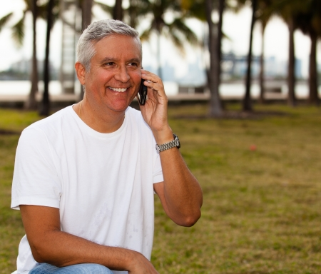south american: Handsome middle age man in casual clothing holding a mobile phone at a park
