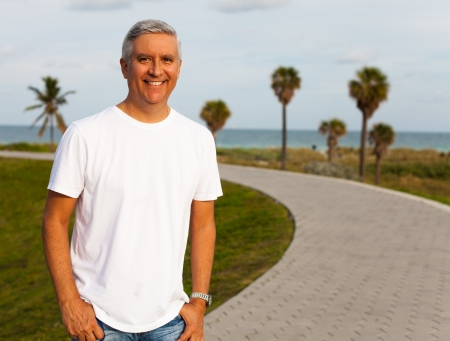 male palm: Handsome middle age man in casual clothing enjoying a Miami Beach park  Stock Photo
