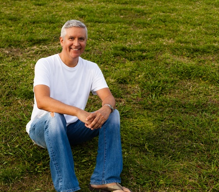 forties: Handsome middle age man in casual clothing enjoying a park setting  Stock Photo